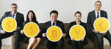 Business people holding currency icons Stock Image