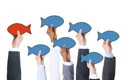 Business People Holding Fish Symbol Stock Image