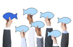 Business People Holding Fish Symbol and Contrasts Concept Royalty Free Stock Images