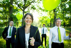 Business People Holding Green Balloon In Forest.  Royalty Free Stock Photo