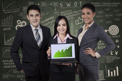 Business people holding growth graph. Group of smiling business people holding a board with growth graph Royalty Free Stock Images