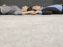 Business People Holding Hands While Lying On Ground Royalty Free Stock Photos