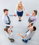 Business people holding hands to form a circle. High angle of business people royalty free stock photography