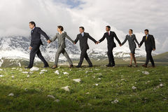 Business People Holding Hands And Walking Through Mountains Royalty Free Stock Photography