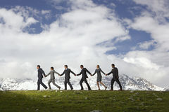 Business People Holding Hands And Walking Through Mountains Stock Photo