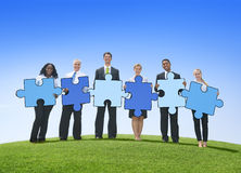 Business People Holding Jigsaw Puzzle Pieces Outdoors.  Royalty Free Stock Images