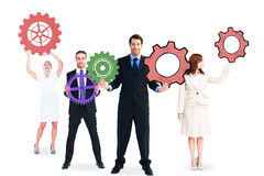 Business people holding large cogs Stock Photography