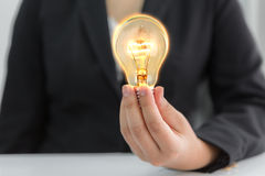 Business people holding light bulb Royalty Free Stock Photos