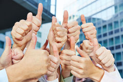 Business people holding many thumbs up stock photo