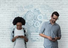 Business people holding phones against white wall with graphics Royalty Free Stock Image