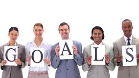 Business people holding posters with the word GOALS. A against white background stock footage