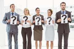 Business people holding question mark signs Stock Photography
