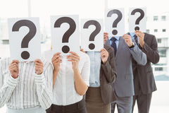 Business people holding question mark signs in office Royalty Free Stock Image