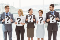 Business people holding question mark signs Royalty Free Stock Photography