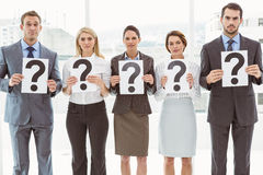 Business people holding question mark signs Stock Images