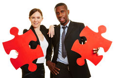 Business people holding red jigsaw puzzle pieces Stock Photography