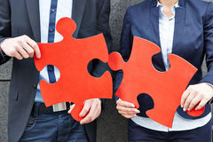 Business people holding red jigsaw Royalty Free Stock Photography