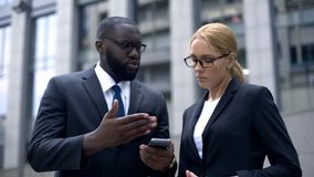 Business people holding smartphone, dissatisfied with inappropriate internet. Stock photo stock photo