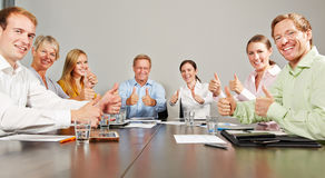 Business people holding thumbs up in meeting Stock Image
