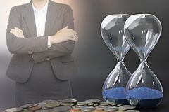 Business people with hourglass and coins in financial time stock image