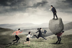 Business people with hurdle on the hill. Image of young leader shouting at his employees with a megaphone while standing above the stone and his partner on the Stock Photography