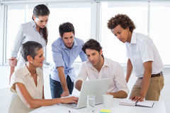 Business people interacting and looking at laptop Stock Photos