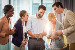 Business people interacting using mobile phone. Group of business people interacting using mobile phone in the office Royalty Free Stock Image