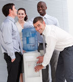 Business people interacting at a water cooler. In the office Royalty Free Stock Photo