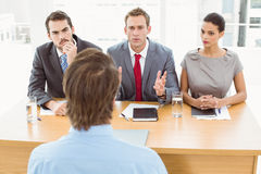 Business people interviewing man in office Stock Photography