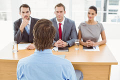 Business people interviewing man in office Stock Images
