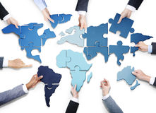 Business People with Jigsaw Forming World Map Stock Photography