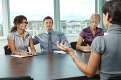 Business people at job interview. Panel of business people sitting at table in meeting room conducting job interview talking with applicant