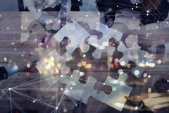 Business people join puzzle pieces in office. Concept of teamwork and partnership. double exposure with internet network. Business people join puzzle pieces in a royalty free stock photography
