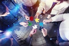 Business people join puzzle pieces in office. Concept of teamwork and partnership. double exposure with light effects. Business people collaborate together in royalty free stock images