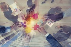 Business people join puzzle pieces in office. Concept of teamwork and partnership. double exposure. Business people join puzzle pieces over a table in office stock photo