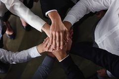 Business people joining hands in the office. concept of teamwork and partnership. Business people joining hands in a circle in the office. concept of teamwork Royalty Free Stock Images