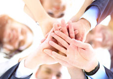 Business people joining hands in a circle in the office. Small group of business people joining hands, low angle view Royalty Free Stock Photos