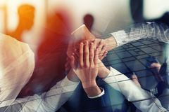 Business people joining hands in the office. concept of teamwork and partnership. double exposure. Business people joining hands in a circle in the office Stock Image