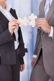 Business people joining jigsaw pieces in office Stock Photography