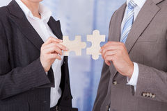 Business People Joining Jigsaw Pieces In Office Royalty Free Stock Photo