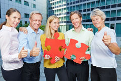 Business people with jugsaw puzzle holding thumbs up Stock Images