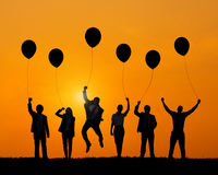 Business People Jumping While Holding Balloons Stock Photo