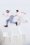 Business people jumping over chairs. Business people jumping over some chairs Stock Photography