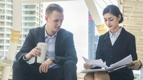 Business people lady and caucasian smart man with smart phone an. Business people lady and caucasian smart men with smart phone and cup of coffee and talk Royalty Free Stock Image