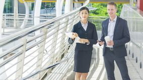 Business people lady and caucasian smart man with smart phone an. Business people lady and caucasian smart men with smart phone and cup of coffee and talk Royalty Free Stock Photography