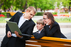 Young business people using laptop in city park Stock Photos