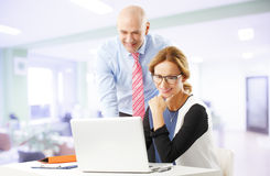 Business people with laptop. Portrait of business people working at laptop. Middle age businesswoman sitting in front of laptop and consulting with senior Royalty Free Stock Photos
