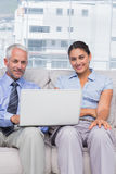 Business people with laptop smiling at camera sitting on couch Royalty Free Stock Photos