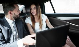 Business man and woman working together in the car. Business people with a laptop working in the back seat of a car Royalty Free Stock Image