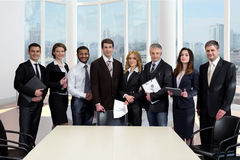 Business people in a large modern glass office. Royalty Free Stock Image